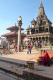 PATAN, НЕПАЛ - 19-ОЕ ДЕКАБРЯ 2014: Статуя Garuda на столбце и висок Krishna Mandir на Durbar придают квадратную форму Стоковые Фото