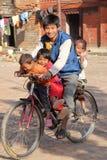 PATAN, НЕПАЛ - 21-ОЕ ДЕКАБРЯ 2014: Усмехаясь семья с 3 милыми детьми на велосипеде Стоковое Изображение RF