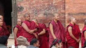 Patan, Nepal - circa 2013: Buddhist monks chat and play preparing for a ceremony. Patan, Nepal - circa 2013: Buddhist monks chat and play while preparing for a stock footage