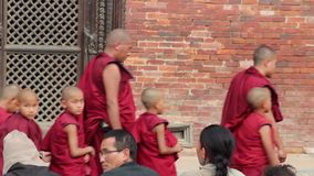 Patan, Nepal - CIRCA 2013: Buddhist monks chat and play preparing for a ceremony. Patan, Nepal - CIRCA 2013: Buddhist monks chat and play while preparing for a stock video footage
