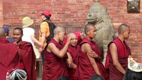 Patan, Nepal - circa 2013: Los monjes budistas charlan y juegan la preparación para una ceremonia almacen de metraje de vídeo