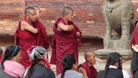 Patan, Nepal - circa 2013: Los monjes budistas charlan y juegan la preparación para una ceremonia almacen de video