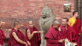 Patan, Nepal - circa 2013: Los monjes budistas charlan y juegan la preparación para una ceremonia metrajes
