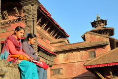 PATAN, NEPAL - 21 DE DEZEMBRO DE 2014: Duas mulheres nepalesas novas que sentam-se no quadrado de Durbar fotos de stock
