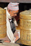 PATAN, NEPAL - 19 DE DEZEMBRO DE 2014: Um Bhudist do homem de Nepalês que lê orações no templo dourado com oração roda dentro o p imagens de stock royalty free