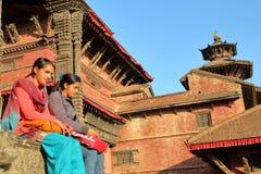 PATAN, NEPAL - 21 DE DICIEMBRE DE 2014: Dos mujeres nepalesas jovenes que se sientan en el cuadrado de Durbar Fotos de archivo