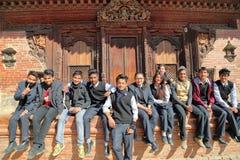 PATAN NEPAL - DECEMBER 21, 2014: Nepalesiska studenter som framme poserar av en tempel på den Durbar fyrkanten Fotografering för Bildbyråer