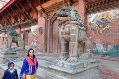 PATAN NEPAL, GRUDZIEŃ, - 22, 2014: Nepalska kobieta i jej syna odprowadzenie wzdłuż Mul Chowk Royal Palace przy Durbar Obciosujem Zdjęcia Stock