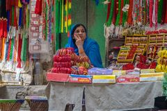 A woman is selling beads at a market stall in anticipation of the coming South Asian autumn festival royalty free stock photography