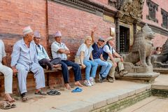 Patan, Nepal - September 21, 2016: Newari men and tourists resting on a bench by the Royal Palace, Durbar Square, Patan, Nepal royalty free stock photos