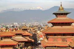 PATAN NEPAL: Tak av tempel på Durbar kvadrerar med de Himalayan bergen i bakgrunden Royaltyfri Foto