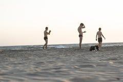 PATARA - FETHIYE, DIE TÜRKEI - 22. AUGUST 2018 Sauberes Trieb des standıng der Männer auf dem Strand auf der Sonnenuntergangzeit stockfotos