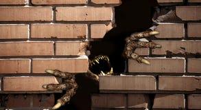 Patas del monstruo, rompiendo una pared de ladrillo Foto de archivo libre de regalías