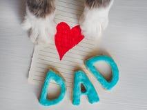 Patas del ` s del gato, tarjeta de felicitación y palabra PAPÁ Fotografía de archivo