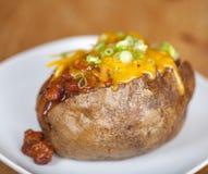 Patata al forno caricata con il peperoncino rosso ed il formaggio Fotografie Stock Libere da Diritti