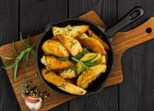Patata asada con romero fresco en cacerola del arrabio Visión superior fotos de archivo