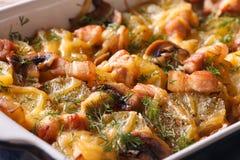 Patata caliente con tocino, las setas y el queso en plato de la hornada Imagen de archivo