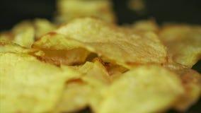 Patata Chips Rotating en fondo negro Las patatas fritas se giran en un fondo negro Primer de delicioso amarillo almacen de video