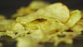 Patata Chips Rotating en fondo negro Las patatas fritas se giran en un fondo negro Primer de delicioso amarillo almacen de metraje de vídeo