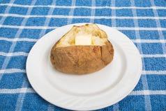 Patata cocida caliente con Pat de la mantequilla Foto de archivo libre de regalías
