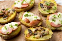 Patata cocida con las setas, tocino, salchicha y con moza del queso Foto de archivo libre de regalías