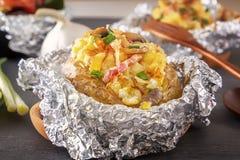 Patata cotta in stagnola con bacon, le cipolle ed i funghi su una tavola di legno grigia fotografia stock libera da diritti