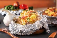 Patata cotta in stagnola con bacon, le cipolle ed i funghi su una tavola di legno grigia fotografie stock