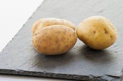Patata cruda sul tavolo da cucina Immagini Stock Libere da Diritti