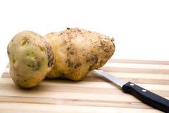 Patata de Brown con el cuchillo Imagenes de archivo