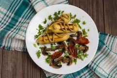 Patata de Zrazy rellena con las setas de la carne y los tomates asados a la parrilla en una placa blanca Fondo de madera Visión s Imágenes de archivo libres de regalías