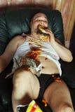 Patata di strato che mangia e che guarda TV fotografia stock libera da diritti