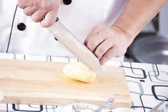 Patata di taglio del cuoco unico su vasto di legno fotografia stock