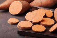 Patata dolce cruda organica intera ed affettata sul bordo di legno della cucina Fotografia Stock