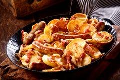 Patata dorata croccante con la salsiccia ed il bacon piccanti fotografia stock libera da diritti