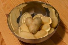 Patata en forma de corazón en un plato con otros potatos en una tabla Foto de archivo