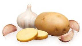 Patata non sbucciata con i pezzi tagliati, aglio con i chiodi di garofano Fotografie Stock