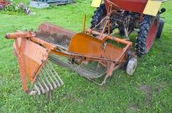 Patata que cosecha la pequeña maquinaria de la cosechadora en granja Fotografía de archivo