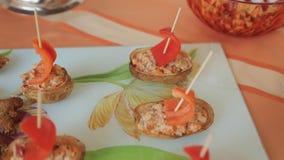 Patata rellena con la ensalada bajo la forma de barco y camarón frito en un banquete almacen de metraje de vídeo