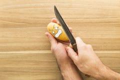 Patata spaventosa del fronte che è tagliata su un bordo di legno della cucina Fotografia Stock