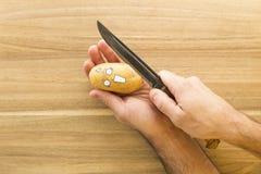 Patata spaventosa del fronte che è tagliata su un bordo di legno della cucina Fotografia Stock Libera da Diritti