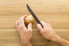 Patata spaventosa del fronte che è tagliata su un bordo di legno della cucina Fotografie Stock