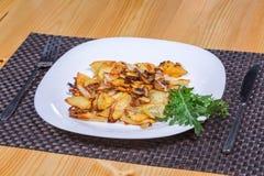 Patata y setas asadas con verdes en la placa blanca Fotografía de archivo