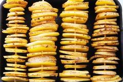 Patatas amarillas crudas en una cáscara, corte en rebanadas Los pedazos son pinchos de madera atados y preparado para cocer Fotos de archivo