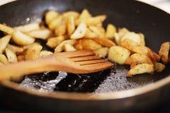 Patatas asadas cerca para arriba en un condimento fragante en cacerola en mantequilla con la cuchara de madera Imagen de archivo libre de regalías