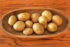 Patatas blancas que ponen en cuenco de madera oval largo en la tabla de roble rojo Imagen de archivo
