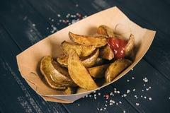 Patatas cocidas al horno Bocado en las cajas respetuosas del medio ambiente de papel Comida para llevar en una caja de papel Alim fotos de archivo