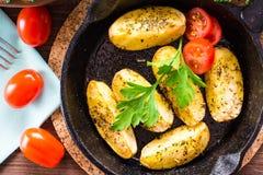 Patatas cocidas cortadas en un sartén del hierro Fotografía de archivo libre de regalías