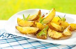 Patatas cocidas de las cuñas con romero en la placa blanca Fotos de archivo
