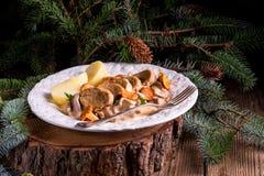 Patatas con los medallones del cerdo y la salsa del mízcalo Foto de archivo
