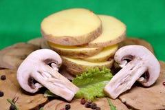 Patatas crudas con los champiñones en un claro de madera imagen de archivo